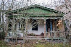 La casa y el pórtico viejos, descuidados, señoriales entre los árboles Textura de la madera agrietada vieja pintada verde Imágenes de archivo libres de regalías