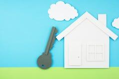 La casa y la llave formaron el recorte de papel en el campo del cielo y de hierba hecho de Imágenes de archivo libres de regalías