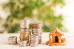 La casa y las monedas apiladas en el fondo de madera, concepto en el crecimiento, venta, compra, reserva e invierten fotos de archivo libres de regalías
