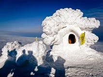 La casa y los turistas nevados en una montaña rematan Foto de archivo libre de regalías