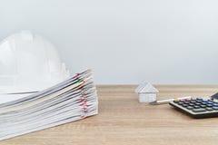 La casa y la pluma tienen sombrero del ingeniero de la falta de definición como fondo Imagen de archivo