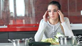 La casalinga abbastanza giovane è stanca cucinando l'insalata nella cucina video d archivio