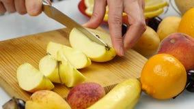 La casalinga a casa che prepara l'insalata fresca che affetta la mela fruttifica sul tagliere alimento sano vegetariano ed essere stock footage