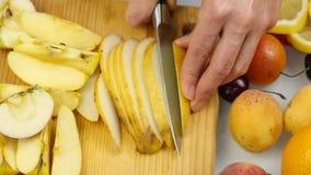 La casalinga a casa che prepara l'insalata fresca che affetta la pera fruttifica sul tagliere alimento sano vegetariano ed essere archivi video