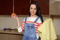 La casalinga castana in vestiti domestici pulisce la mela dall'asciugamano immagine stock libera da diritti