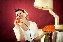 La casalinga d'annata chiacchiera sul telefono nel salone di capelli Immagini Stock Libere da Diritti