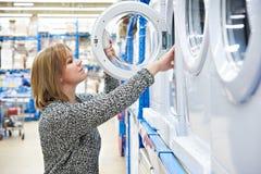 La casalinga della donna sceglie la lavatrice in negozio di applianc domestico immagine stock