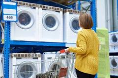 La casalinga della donna sceglie la lavatrice in deposito fotografie stock libere da diritti