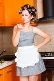 La casalinga di mezza età femminile dipinge le sue labbra nella cucina Immagini Stock