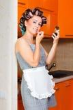 La casalinga di mezza età femminile dipinge le sue labbra nella cucina Immagini Stock Libere da Diritti