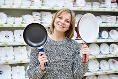 La casalinga felice della donna sceglie la padella fotografia stock