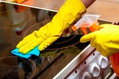 La casalinga pulisce la fresa ceramica di vetro - mani gloved con uno straccio fotografia stock