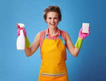 La casalinga sorridente che mostra la pulizia pulisce e detersivo sul blu fotografia stock libera da diritti