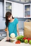 La casalinga utilizza un computer della compressa nella cucina immagini stock