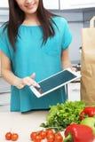 La casalinga utilizza un computer della compressa nella cucina fotografie stock
