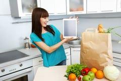 La casalinga utilizza un computer della compressa nella cucina immagine stock