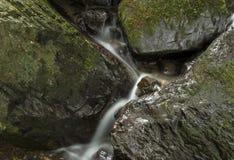 La cascada cae con las rocas Imagenes de archivo
