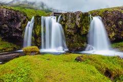 La cascada cae en la colina herbosa Foto de archivo