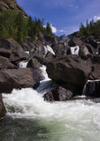 La cascada cae sobre el río con las rocas Imagen de archivo