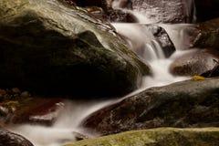 La cascada cae sobre el río viejo del ciruelo con las rocas Foto de archivo libre de regalías
