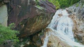 La cascada cercana de la visión corre en el lago Boulder grande en primero plano metrajes