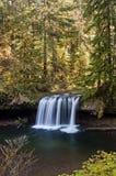 La cascada con los árboles encendidos de oro y la turquesa riegan. Imagen de archivo libre de regalías