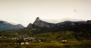La cascada de las nubes viene del pico de montaña a vallay con el pueblo almacen de metraje de vídeo