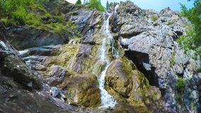 La cascada de Shirlak en rocas en el cielo azul con blanco se nubla el fondo Monta?as de Altai metrajes