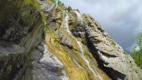 La cascada de Shirlak en rocas en el cielo azul con blanco se nubla el fondo Monta?as de Altai almacen de video