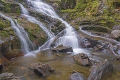 La cascada fluye abajo de roca de fondo coloreada caliente Foto de archivo libre de regalías