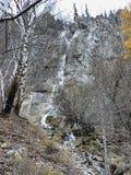 La cascada fluye abajo del acantilado Árboles en cada lado Fotografía de archivo