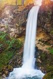 La cascada hermosa en un otoño cubrió el lado de la montaña Imágenes de archivo libres de regalías