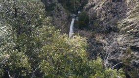 La cascada hermosa entre los acantilados, visión aérea, abejón está moviendo hacia atrás almacen de video