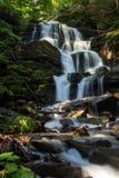 La cascada hermosa sale de una roca enorme en el bosque fotos de archivo