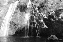La cascade blanche glisse sur des roches noires et blanches photo stock