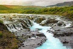 La cascade de Bruarfoss avec de l'eau turquoise cascade au coucher du soleil, glace Photos stock