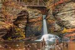 La cascade douce coule sous la passerelle dans l'eau calme ornée avec des cairns Photo libre de droits