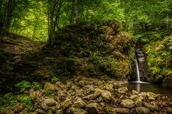 La cascade en montagnes carpathiennes se précipitant vers le bas sur une gouttière a découpé dans une grande roche moussue Photos libres de droits