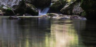 La cascade tombe au-dessus des roches moussues Photographie stock