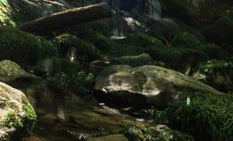 La cascade tombe au-dessus des roches moussues Photos libres de droits