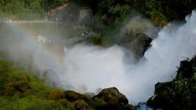 La cascata con le rapide sulle pietre dello spruzzo in aria fa un arcobaleno dai raggi di The Sun archivi video