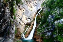 La cascata di Savica di schiaffo in Slovenia circola sulle scogliere muscose Immagini Stock