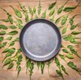 La casserole vide avec l'arugula d'herbes autour de l'endroit pour le texte, encadrent la vue supérieure de fond rustique en bois Photos libres de droits