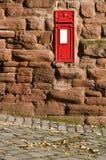 La cassetta postale rossa britannica ha montato nella parete di pietra. Fotografie Stock