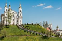 La catedral blanca con las bóvedas está situada en la montaña verde, en los lados de las escaleras están las linternas y los árbo Foto de archivo