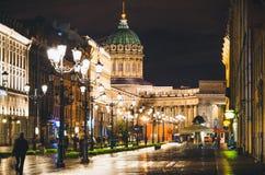 La catedral y Nevsky de Kazán prospectan en las casas viejas St Petersburg de las luces de la noche foto de archivo
