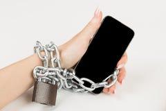 la catena del ferro con la serratura collega la mano femminile e lo smartp fotografia stock