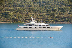 La catena delle piccole barche nell'ambito di rimorchio accanto all'yacht fotografia stock libera da diritti