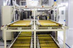 La catena di convogliatore e nastro trasportatore sulla linea di produzione nella stanza pulita Fotografia Stock
