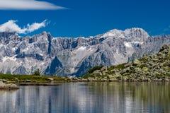 La catena montuosa di Hohe Dachstein con Spiegelsee nel foregro fotografia stock libera da diritti